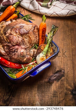 Roasted leg of lamb with herbs and vegetables on wooden background - stock photo