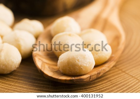 Roasted Macadamia nuts on rustic wooden background - stock photo