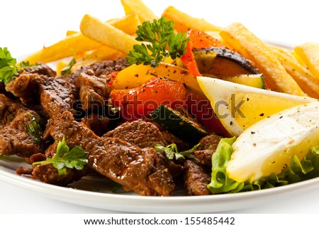 Roasted meat, French fries and vegetables  - stock photo