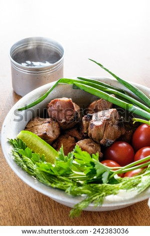 Roasted meat on the fire with vegetables and herbs with hot tea