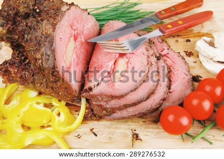 roasted meat served on wooden plate with vegetables - stock photo