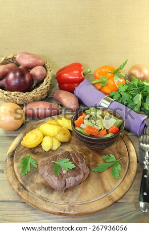 roasted ostrich steaks with baked potatoes and vegetables on a wooden board - stock photo