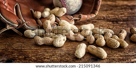 Roasted peanuts in the shell on rustic wood. Baseball and glove in the background. Banner format and rich vintage color. Concepts: snacks, baseball, nostalgia, ballpark, summer, tradition. - stock photo