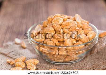 Roasted Peanuts with spices and salt (close-up shot) on dark wooden background - stock photo