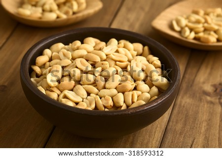Roasted peeled unsalted peanuts in rustic bowl, photographed with natural light (Selective Focus, Focus one third into the peanuts in the bowl)