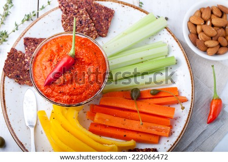 Roasted pepper dip, sauce, spread in a ceramic bowl with fresh carrot, celery sticks on a white wooden background - stock photo