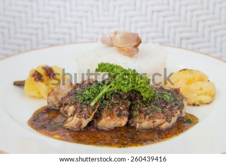 Roasted pepper pork served with rice and pineapple - stock photo