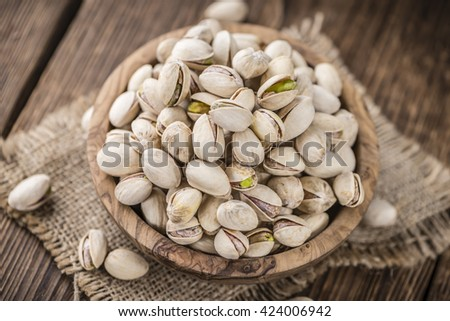 Roasted Pistachios as detailed close-up shot (selective focus) on wooden background - stock photo
