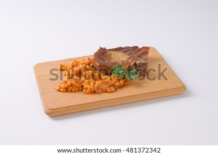 roasted pork cutlet and beans in tomato sauce on wooden cutting board