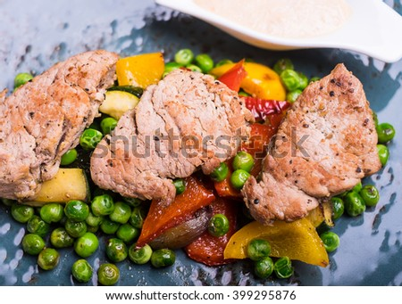 Roasted pork meat fillet chops with zucchini, onion, yellow and orange bell pepper, frozen peas on a plate with cream sauce, selective focus - stock photo