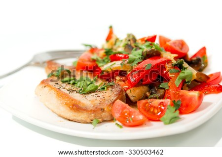 Roasted pork meat with mushrooms and vegetables on white plate.