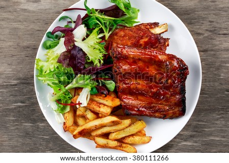 Roasted Pork Rib,  Fried Potato on white plate with Vegetables - stock photo