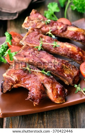 Roasted pork ribs on plate, shallow depth of field - stock photo