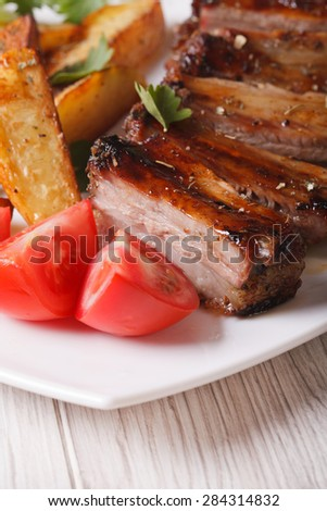 roasted pork ribs, potatoes and fresh tomatoes on the plate macro. vertical - stock photo