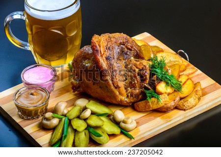roasted pork shank with potatoes on wooden board with beer - stock photo