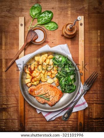 Roasted pork steak, baked potatoes and cooked spinach in rustic metal plate on wooden background, top view - stock photo