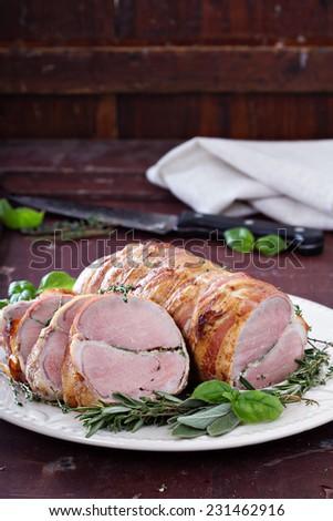 Roasted pork tenderloin with baked garlic, herbs and bacon - stock photo