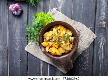 Roasted potato served with herbs and vegetables in dark wooden background