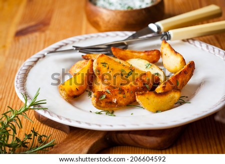 Roasted potato wedges with herbs and garlic on a plate - stock photo