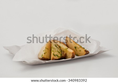 Roasted potato wedges with herbs in disposable plates and paper on a white background close up - stock photo
