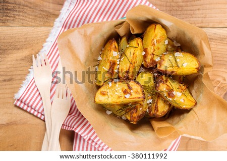 Roasted potato wedges with rosemary and salt in a rustic style - stock photo