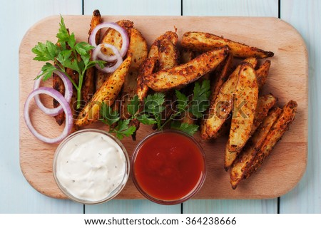 Roasted potato wedges with salsa and onion dip - stock photo