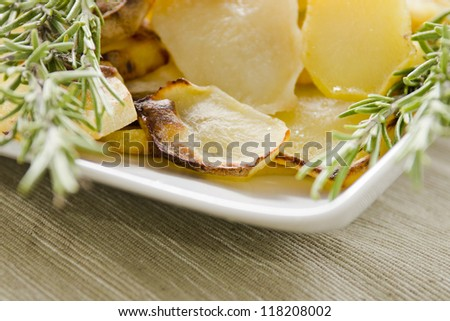 Roasted potatoes with herbs in white dish. Selective focus