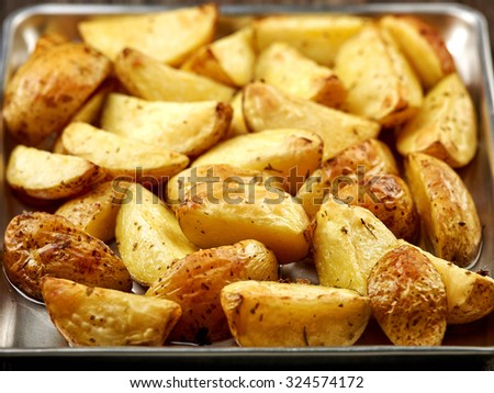 roasted potatoes with spices on oven pan - stock photo
