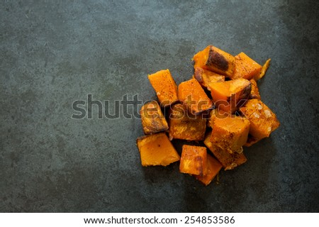 Roasted pumpkin on a black slate background - stock photo