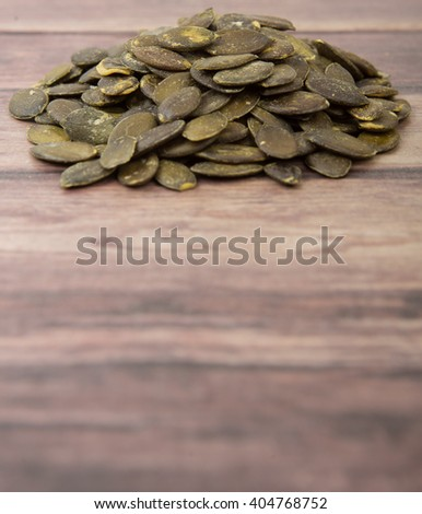 Roasted pumpkin seed over wooden background
