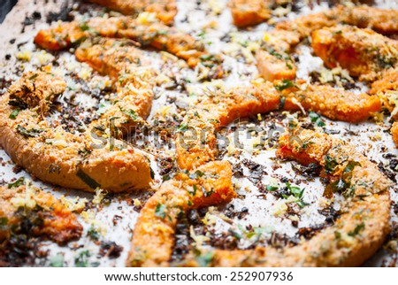 Roasted pumpkin slices with fresh herbs on baking paper. Selective focus - stock photo