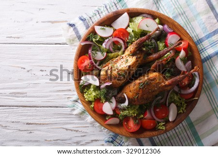 roasted quail and fresh vegetables on a plate. horizontal view from above