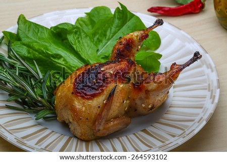 Roasted Quail with rosemary and spices on the wood background - stock photo