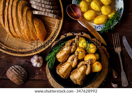 Roasted quails and golden potatoes in iron skillet. Potato salad and fresh sliced bread on side. Country style dinner, table top view.  - stock photo
