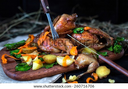 Roasted quails with potato, carrot and green cabbage leaves on a wooden board against a dark background - stock photo