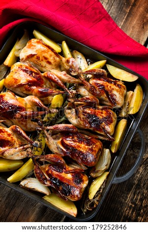 Roasted quails with potatoes, onions and herbs - stock photo