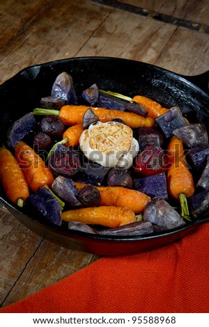 Roasted root vegetables in a cast iron skillet. Vegetables include carrots, red beets, garlic and purple potatoes. - stock photo