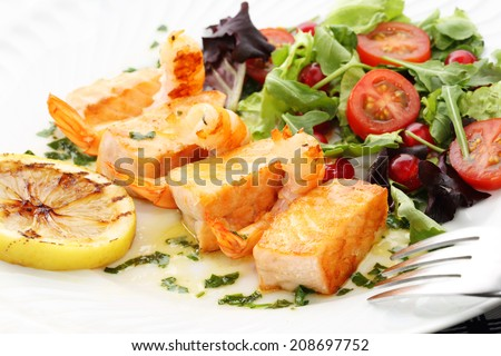 roasted salmon and shrimps with fresh gooseberry salad - stock photo