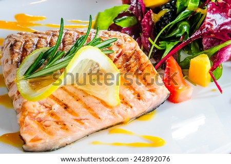 Roasted salmon with ruccola side dish. - stock photo