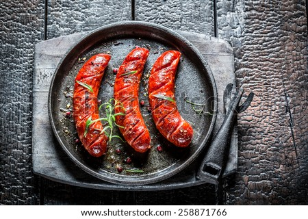 Roasted sausage with fresh herbs on hot barbecue dish - stock photo