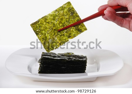 Roasted Seaweed, held with red chopsticks.  Isolated on white - stock photo