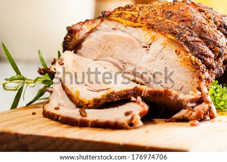 Roasted shoulder of lamb on a cutting board - stock photo