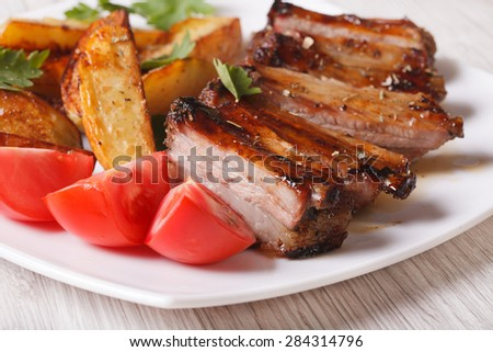 roasted spareribs, potatoes and fresh tomatoes on a white plate close up. horizontal