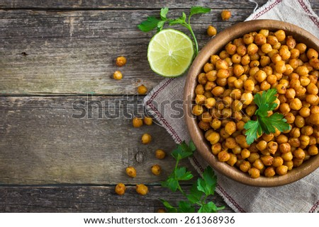 Roasted  spicy chickpeas on rustic background, top view, copy space - stock photo
