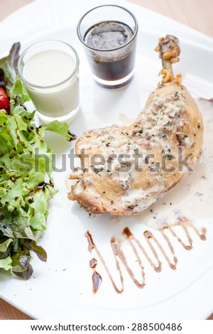 Roasted steak chicken on the table with sauce and salad - stock photo
