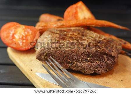 Roasted steak from beef on a wooden board with grilled vegetables