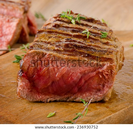 Roasted  steak on   wooden  board . Selective focus