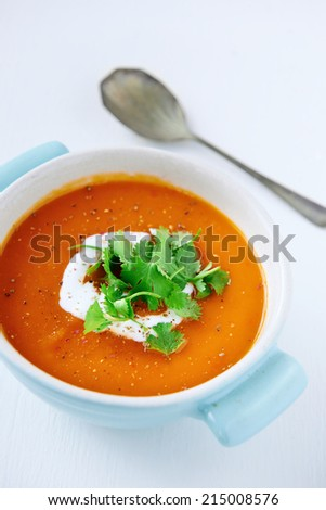 Roasted sweet potato tomato soup with coconut milk cream and coriander garnish, healthy meal on white background - stock photo
