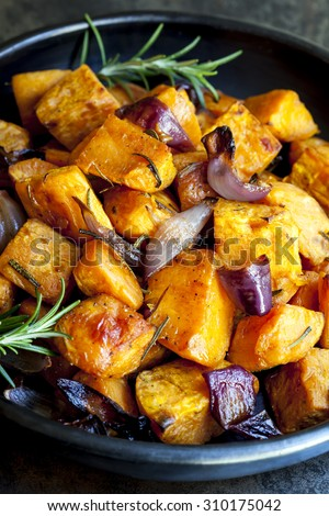 Roasted sweet potato with red onion and rosemary. - stock photo