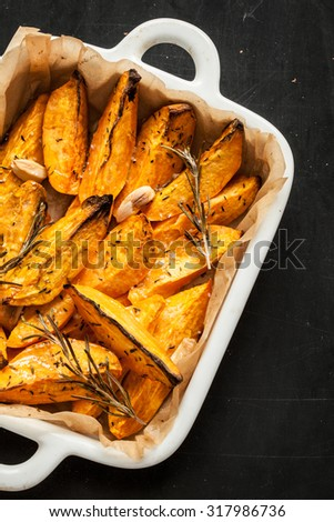 Roasted sweet potatoes in white ceramic dish close up from above. Black chalkboard as background. - stock photo